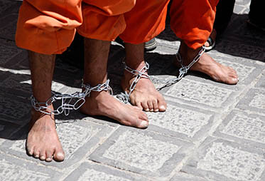 Orange jump-suited detainees handcuffed feet