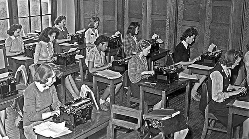 Vintage photograph of girls sitting at desks typing on typewriters
