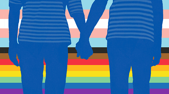 Two people holding hands with LGBTQ+ pride flag behind them