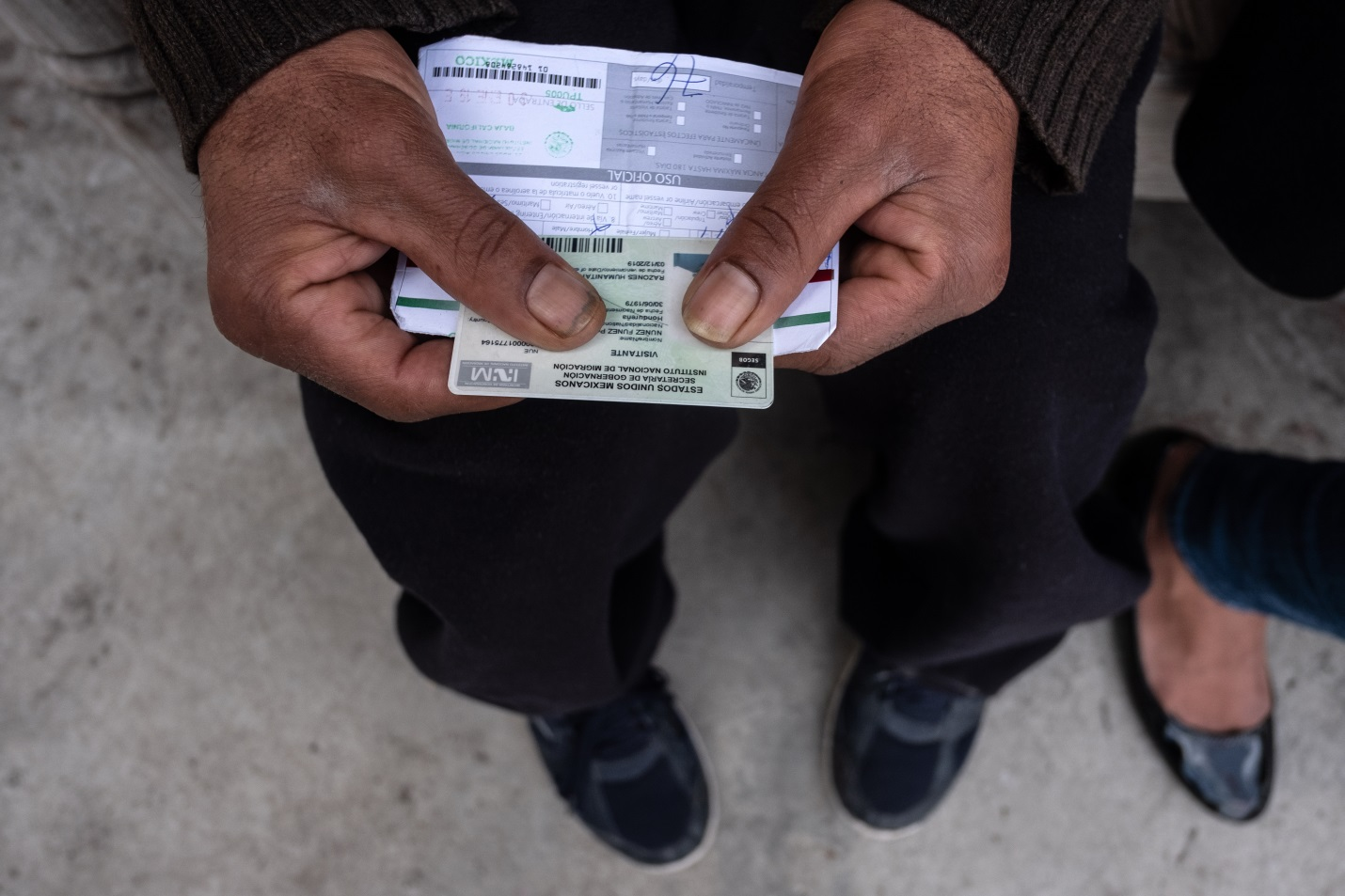 Asylum seeker holds a humanitarian visa card and a piece of paper indicating how long he is legally able to be in Mexico