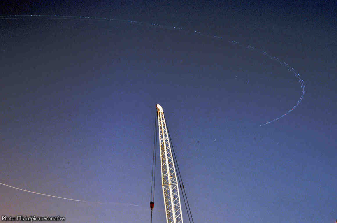 Image of plane circling in sky over radio tower