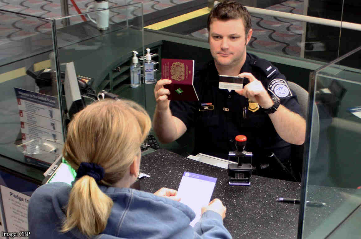 CBP officer at customs comparing IDs with woman's real face