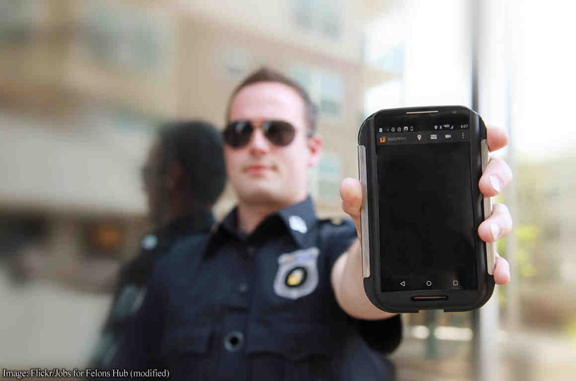 Police officer holding cell phone