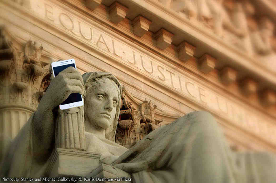 Justice figure statue holding cell phone
