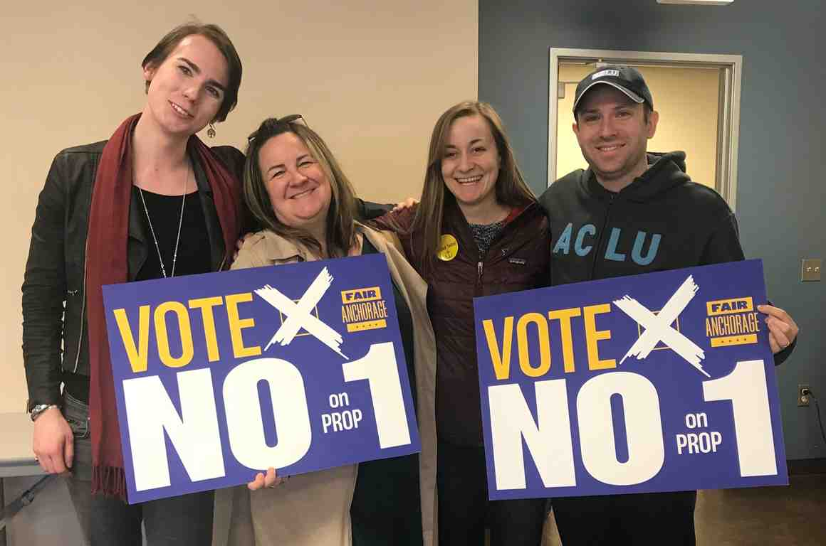 "From left: Lillian Lennon (Transgender Community Organizer, ACLU of Alaska); Liz Welch (ACLU); Kati Ward (Fair Anchorage Campaign Manager); Joshua Decker (Executive Director, ACLU of Alaska). All holding ""Vote no on prop 1 signs."""