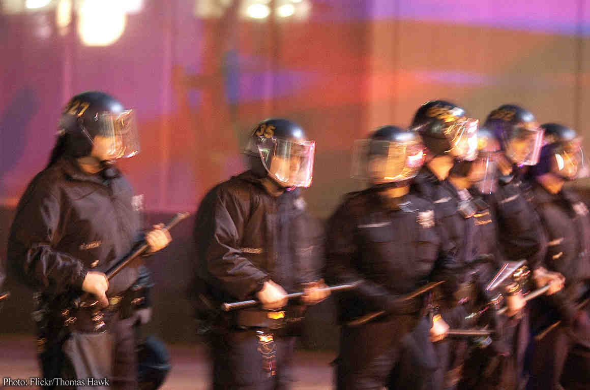 Police in riot helmets holding batons