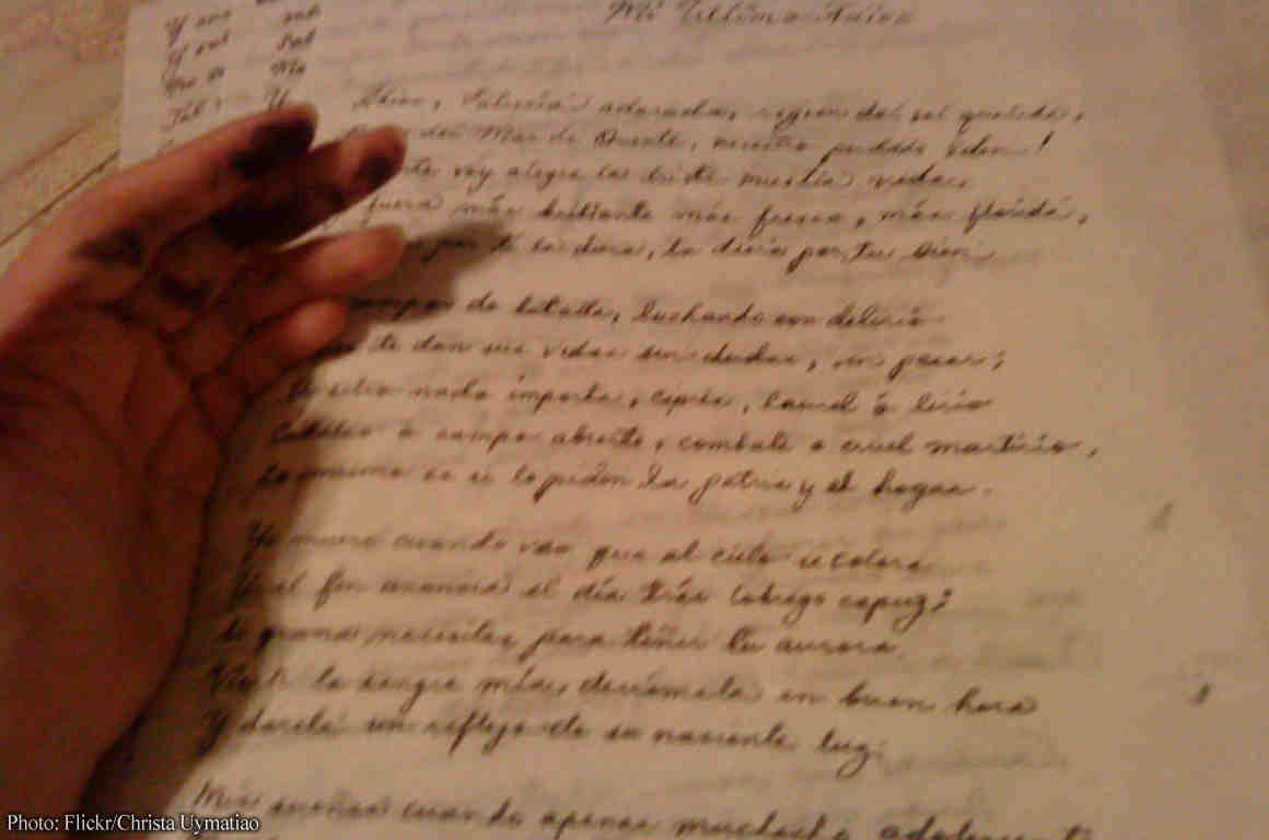 A reader's hand on a parchment letter