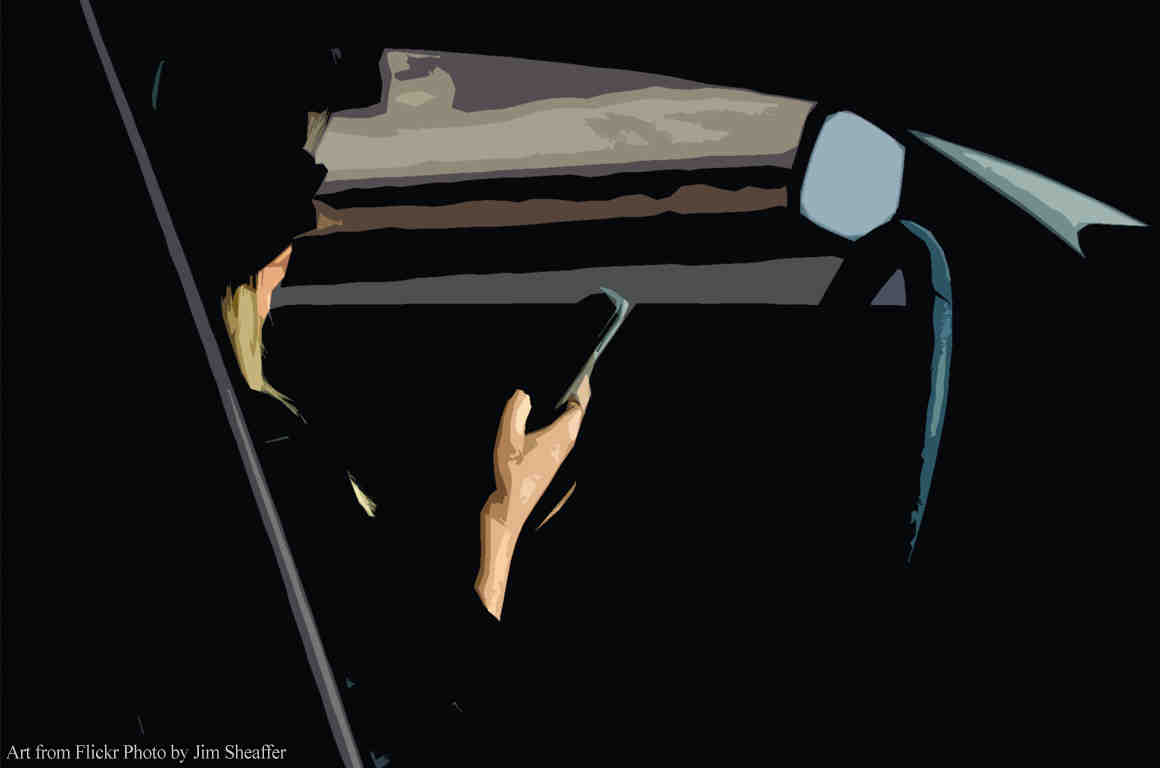 Silhouette of woman holding phone behind the wheel