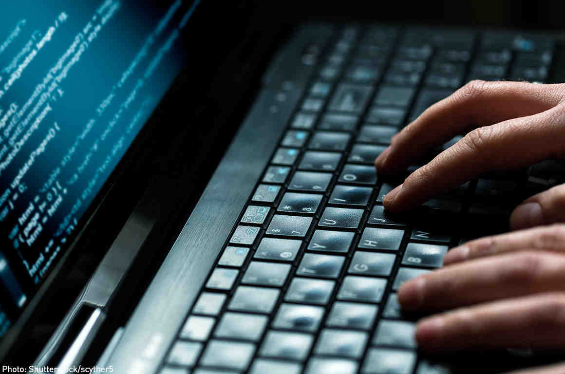 Hacker coding on laptop
