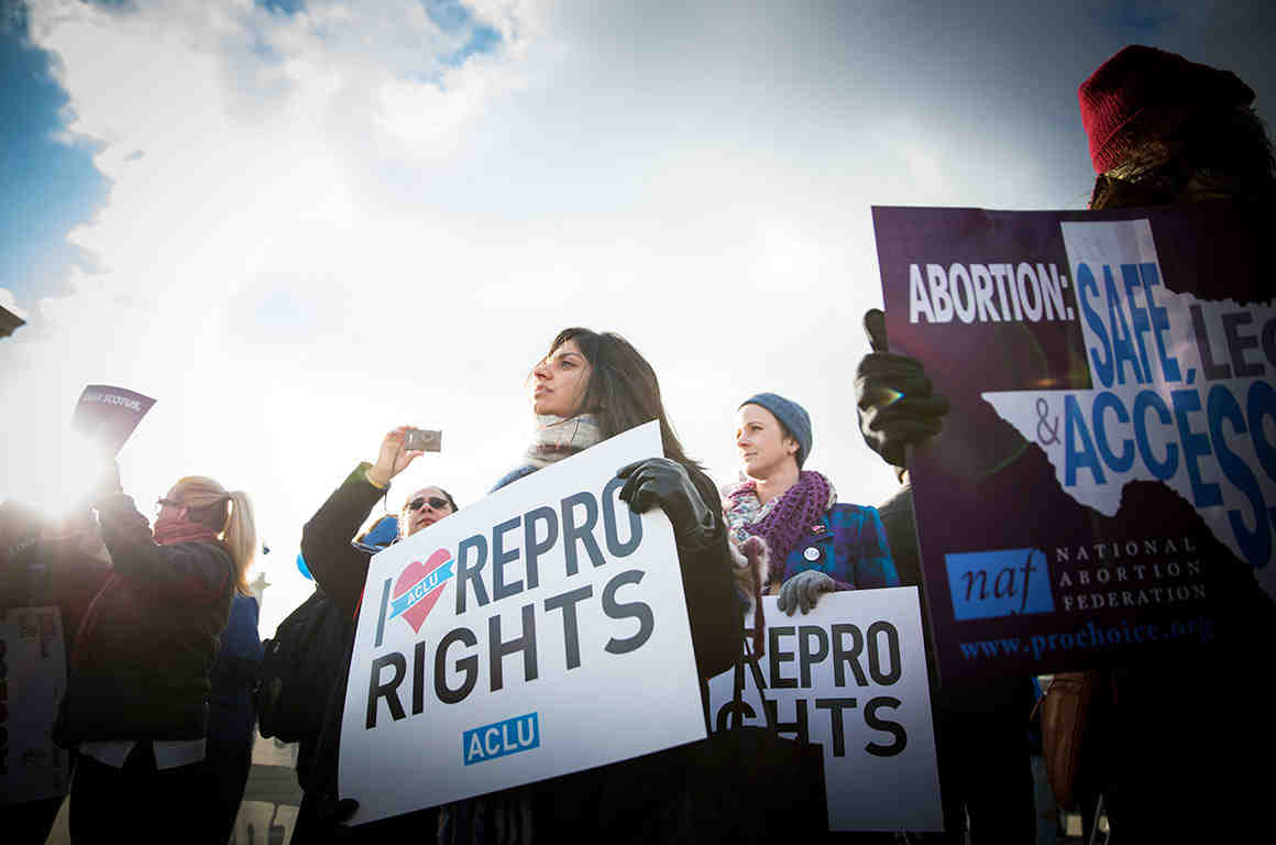 Protesters at an abortion rally holding signs
