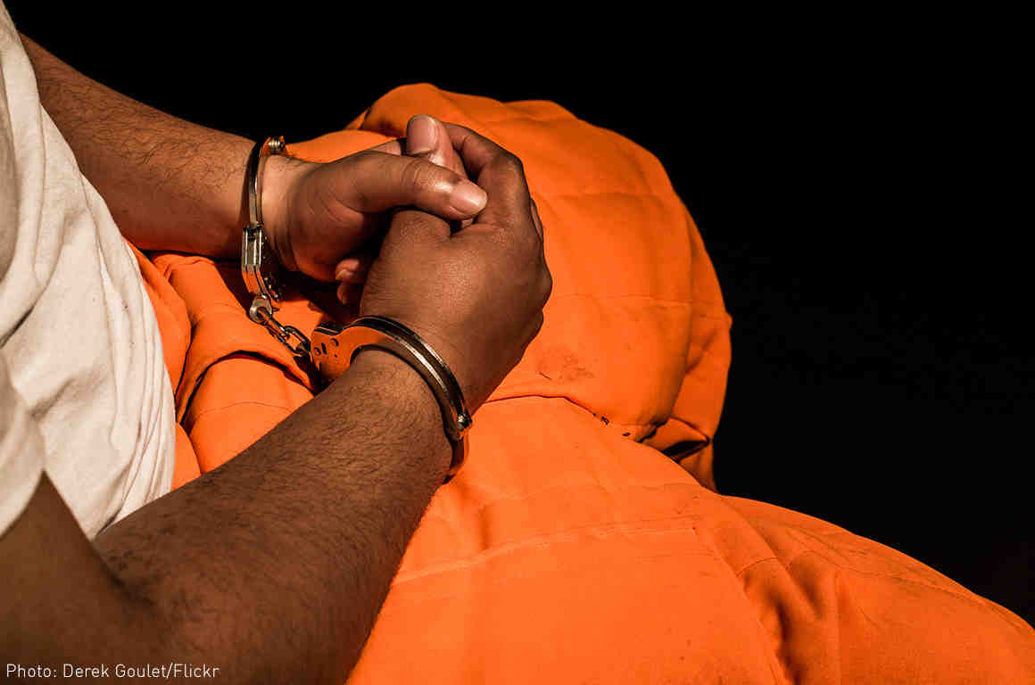 Man with hands cuffed in his lap