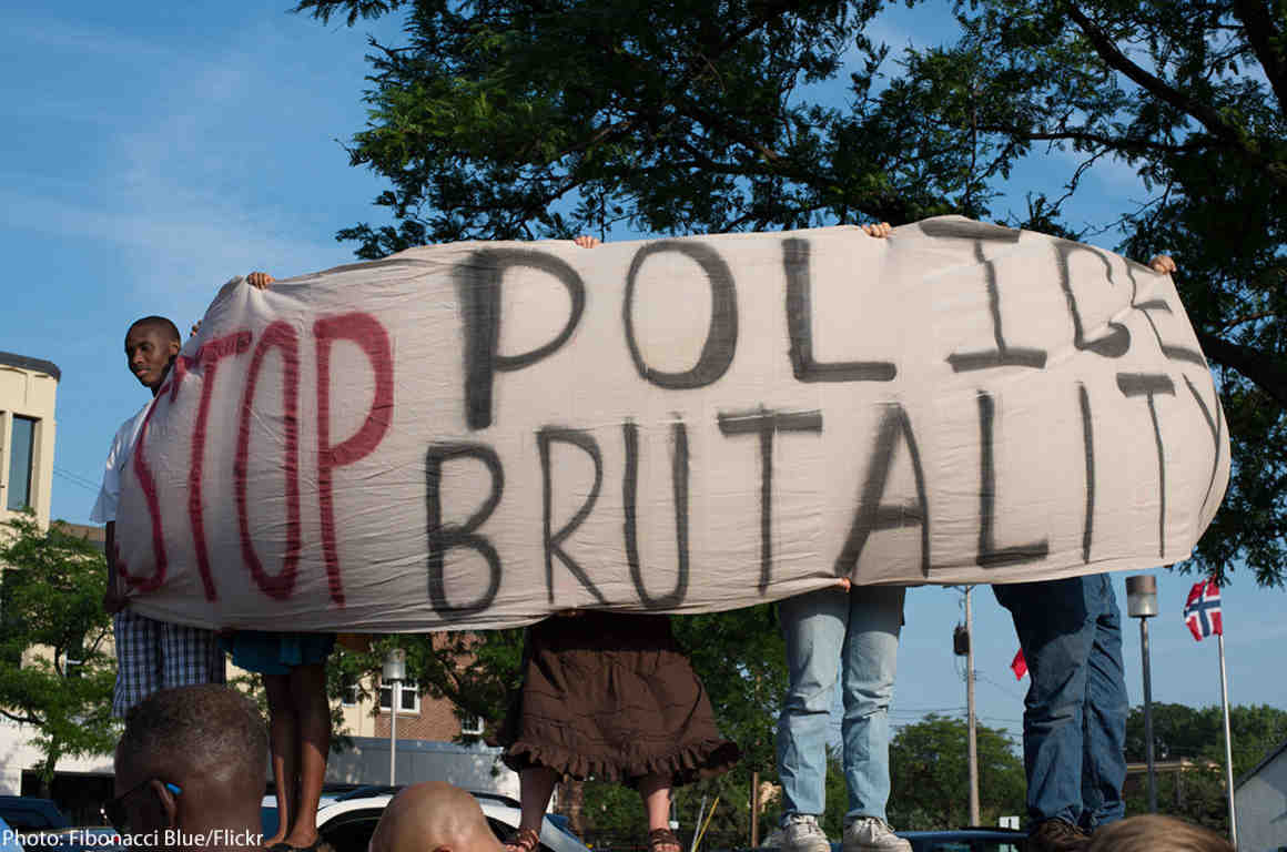 """Protesters holding """"Stop Police Brutality"""" sign"""