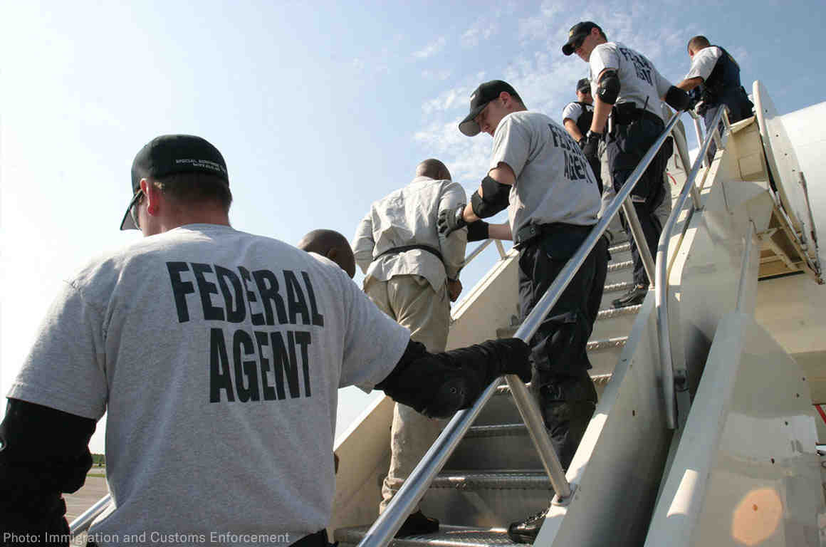 Federal agents deporting individuals on a plane