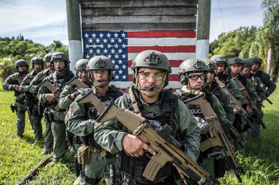 ICE Agents in V formation in front of a painter american flag
