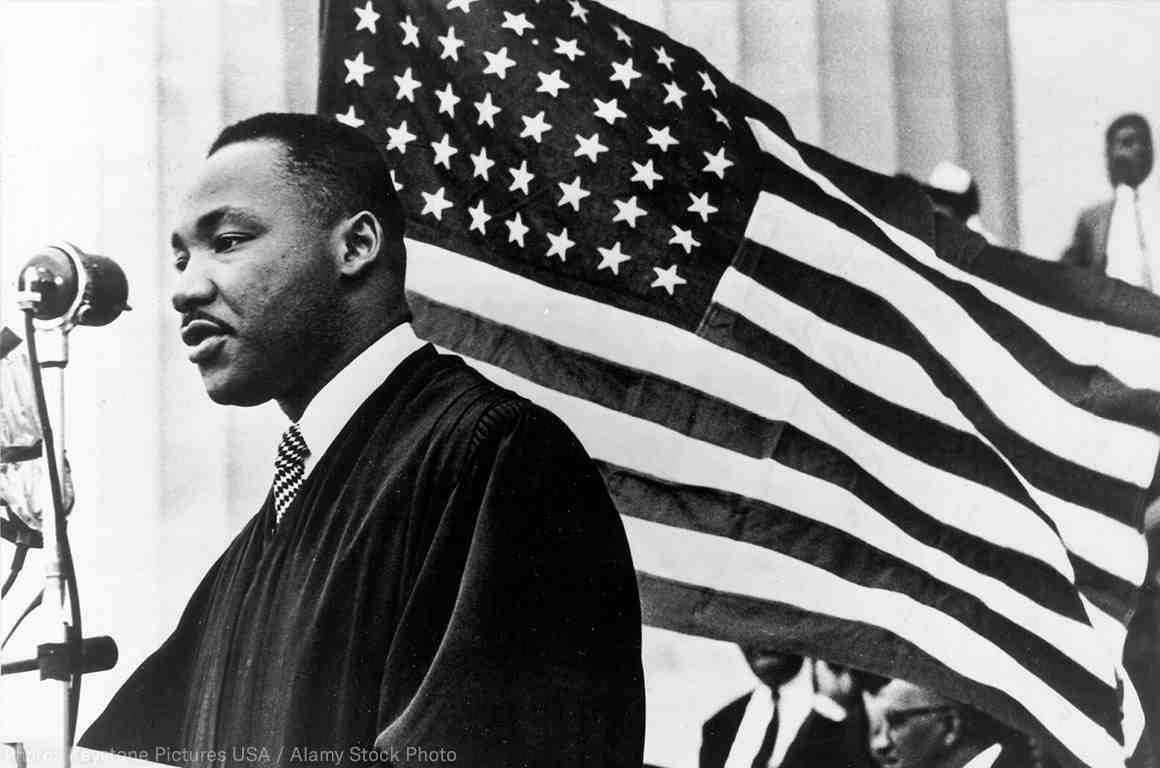 MLK in front of American flag