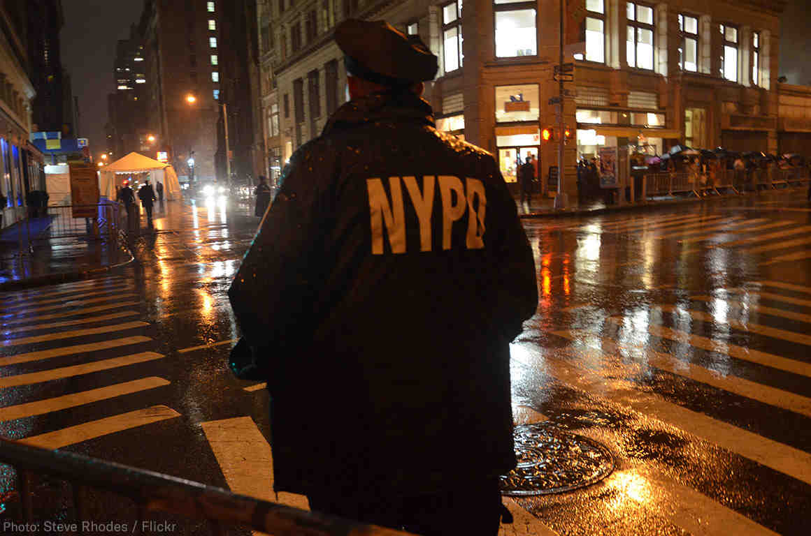 NYPD Officer standing on corner at night