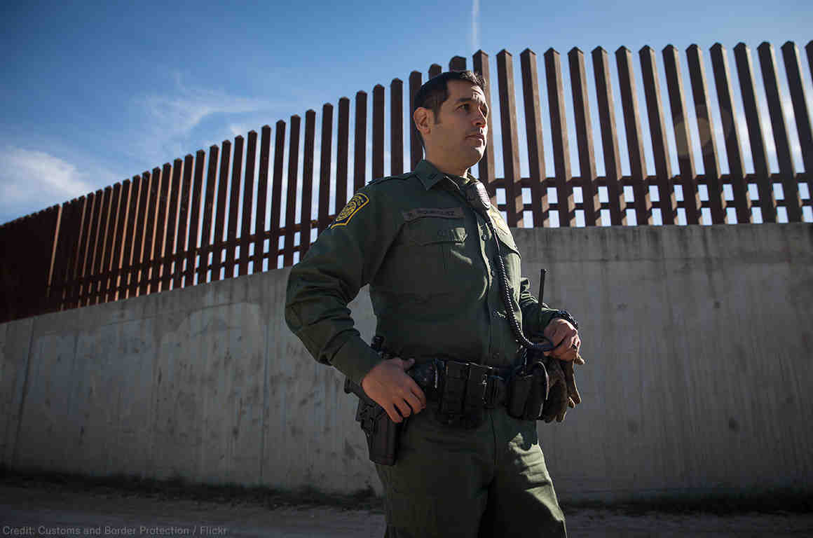 CBP Agent standing before southern border wall.