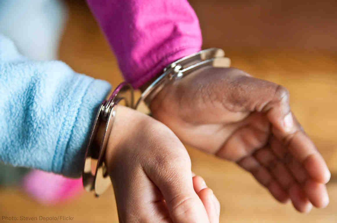 Hands of a child in handcuffs