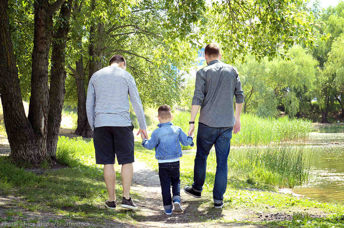 Two men walking with their child