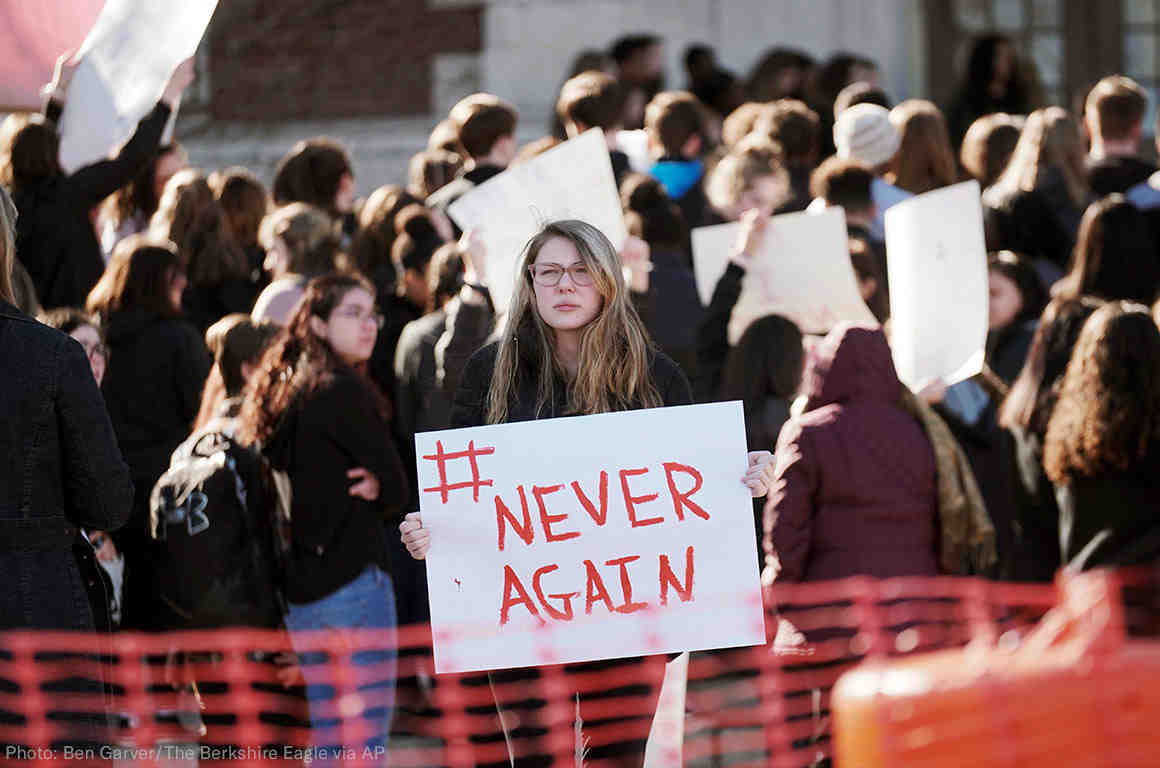 """Student protester holding """"#Never Again"""" sign at rally"""