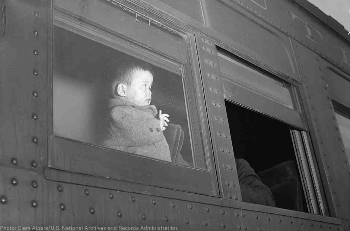 A young child of Japanese ancestry evacuates by train to internment