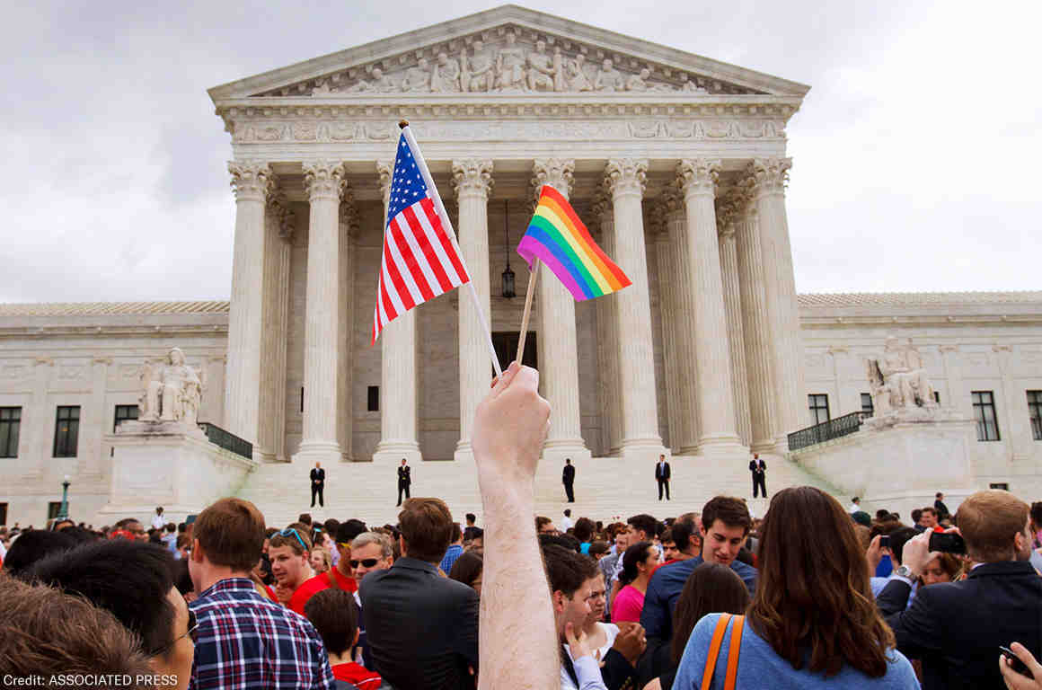 An american flag and pride flag in front of the supreme court