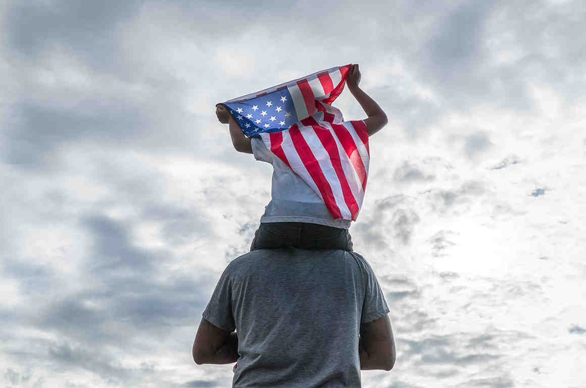 Child holding American flag sitting on dad's shoulders