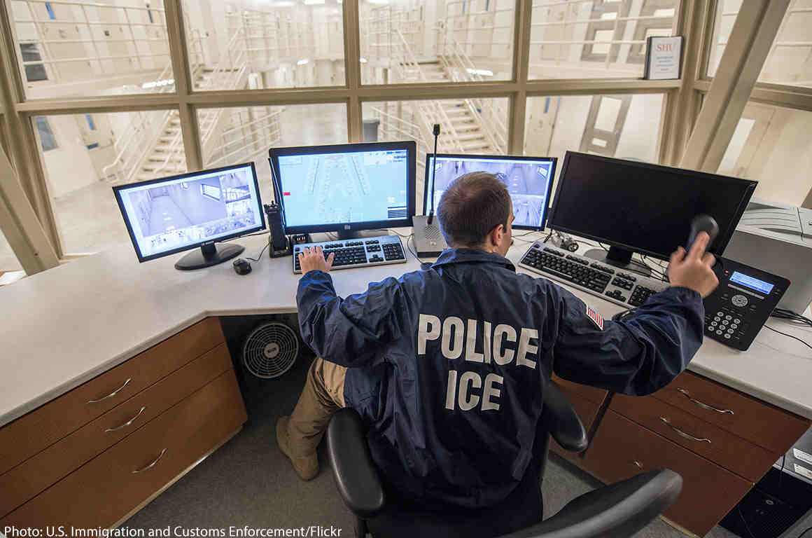 ICE officer looking at computer screens