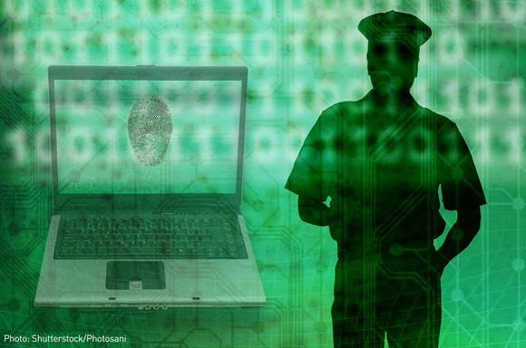 Silhouette of a police officer beside a laptop with fingerprint