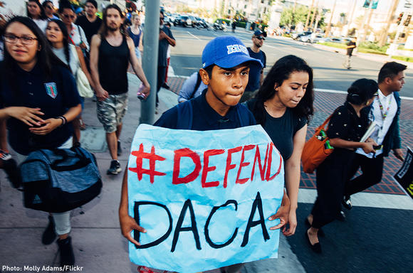 "Boy holding ""#Defend DACA"" sign"