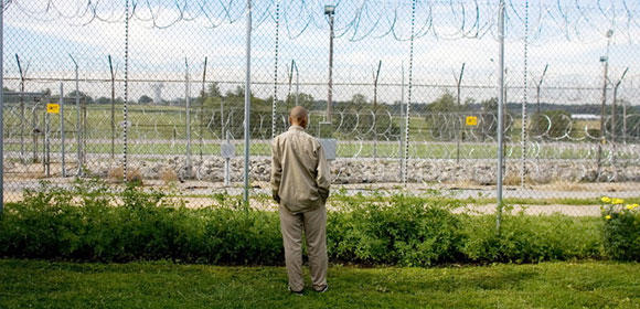 Man in prison uniform facing a barbed wire fence