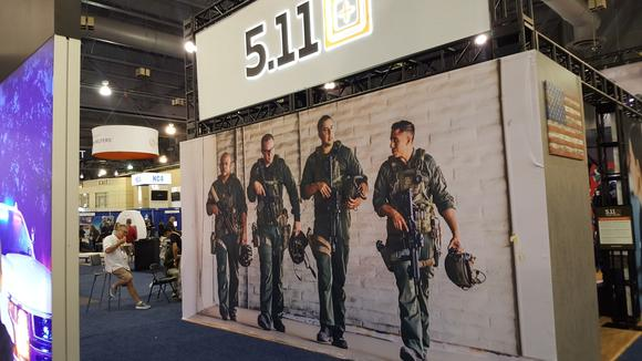 Expo booth featuring larger-than-life photo of four men in military uniforms and gear