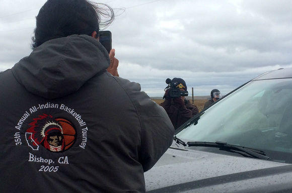 Police and a water protector filming each other at a peaceful protest in front on a police roadblock in St. Anthony, North Dakota.