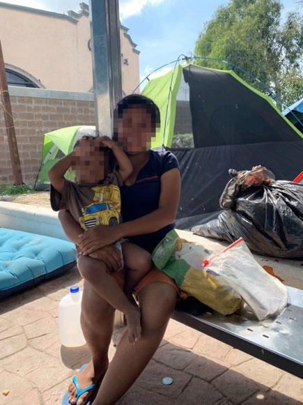 "A young pregnant mother holds her toddler in a makeshift migrant encampment created to house asylum seekers sent back to Mexico as a result of the ""Remain in Mexico"" policy."