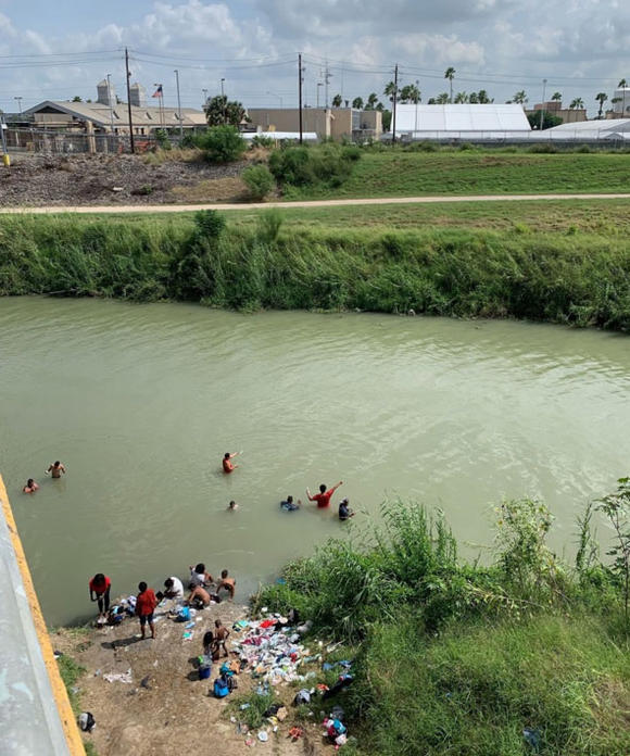 Women, children, and men bathing on the Mexican side of the Rio Grande, just across from Brownsville, Texas.