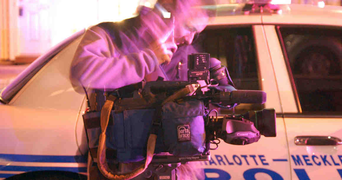 Reporter in front of police car at police activity scene