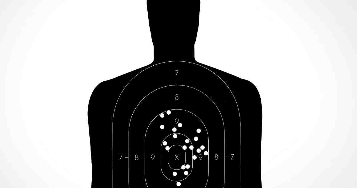 Person-shaped target with bullet holes