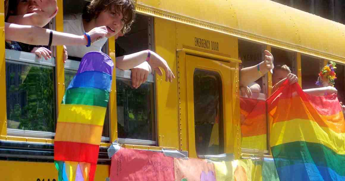 Teens on school bus with LGBT flags