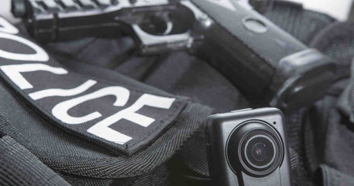 Police vest, body camera, and gun