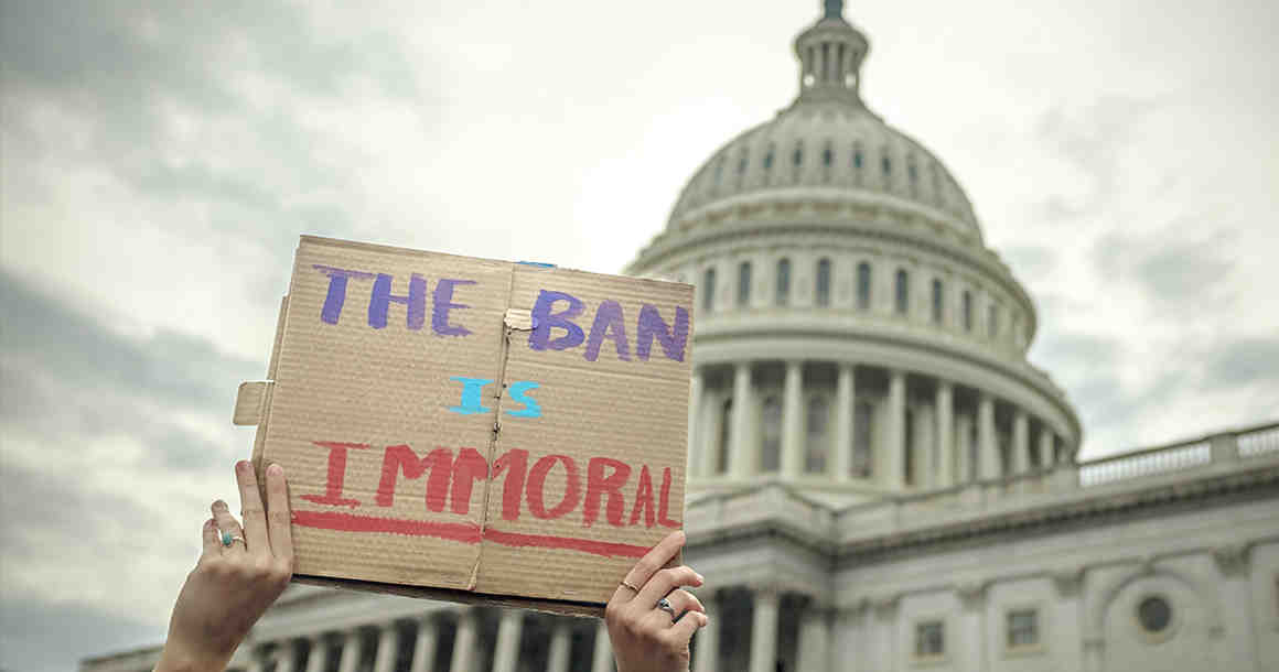 "Person holding ""The Ban Is Immoral"" sign in front of Capitol building"
