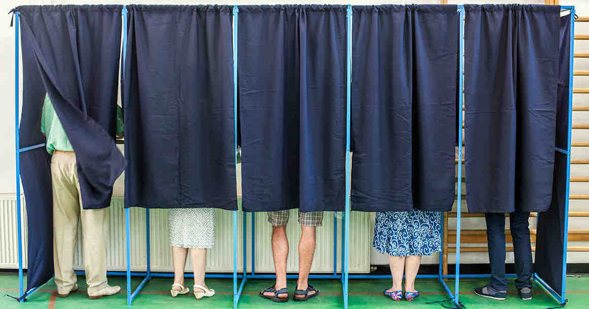 People behind polling booth curtains