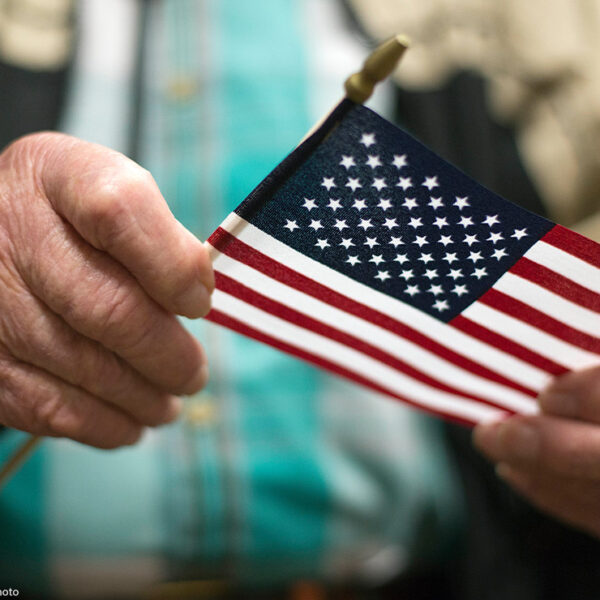 A man holding the American flag after a naturalization ceremony.