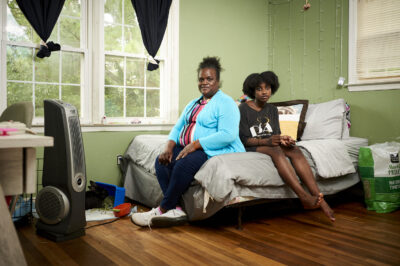 Mother and child sitting on a bed in a bedroom