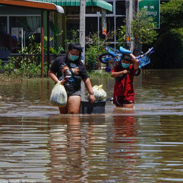 Residents carrying their belongings wade through floodwaters as Pasak Jolasid Dam overflows.
