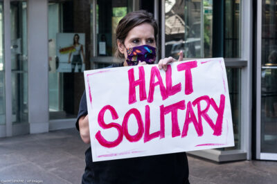 """Woman holds sign that reads """"halt solitary"""" as demand to end solitary confinement in prisons"""